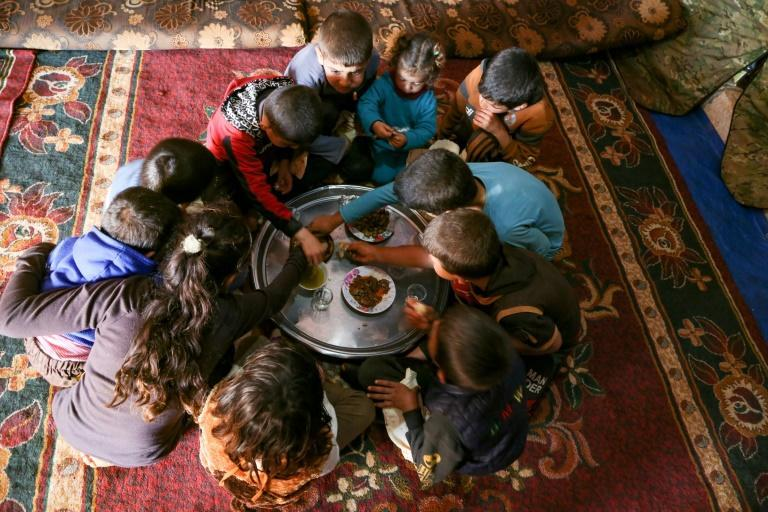The children share a simple meal of flatbread, hummus, olives and dried thyme drenched in olive oil