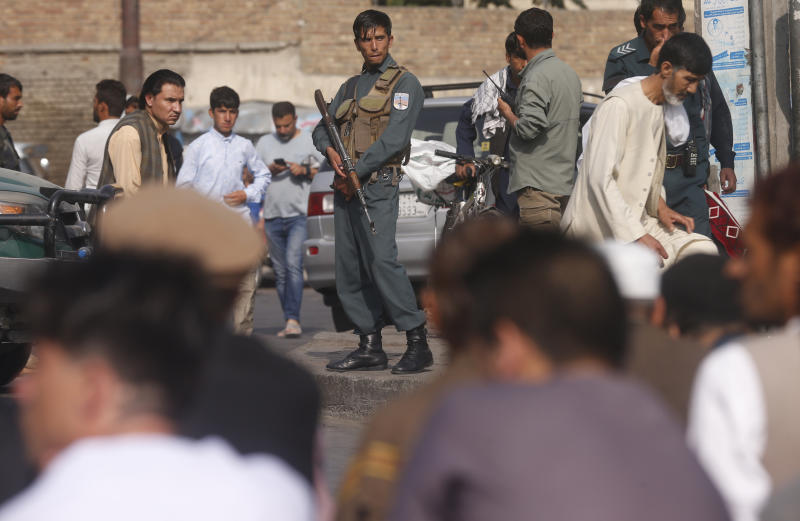 A policeman stands guard as Afghan Muslims attend Eid al-Adha prayers in Kabul, Afghanistan, Sunday, Aug. 11, 2019. Muslim people in the country celebrate Eid al-Adha, or the Feast of the Sacrifice by slaughtering sheep, goats and cows whose meat will later be distributed to the poor.(AP Photo/Rafiq Maqbool)