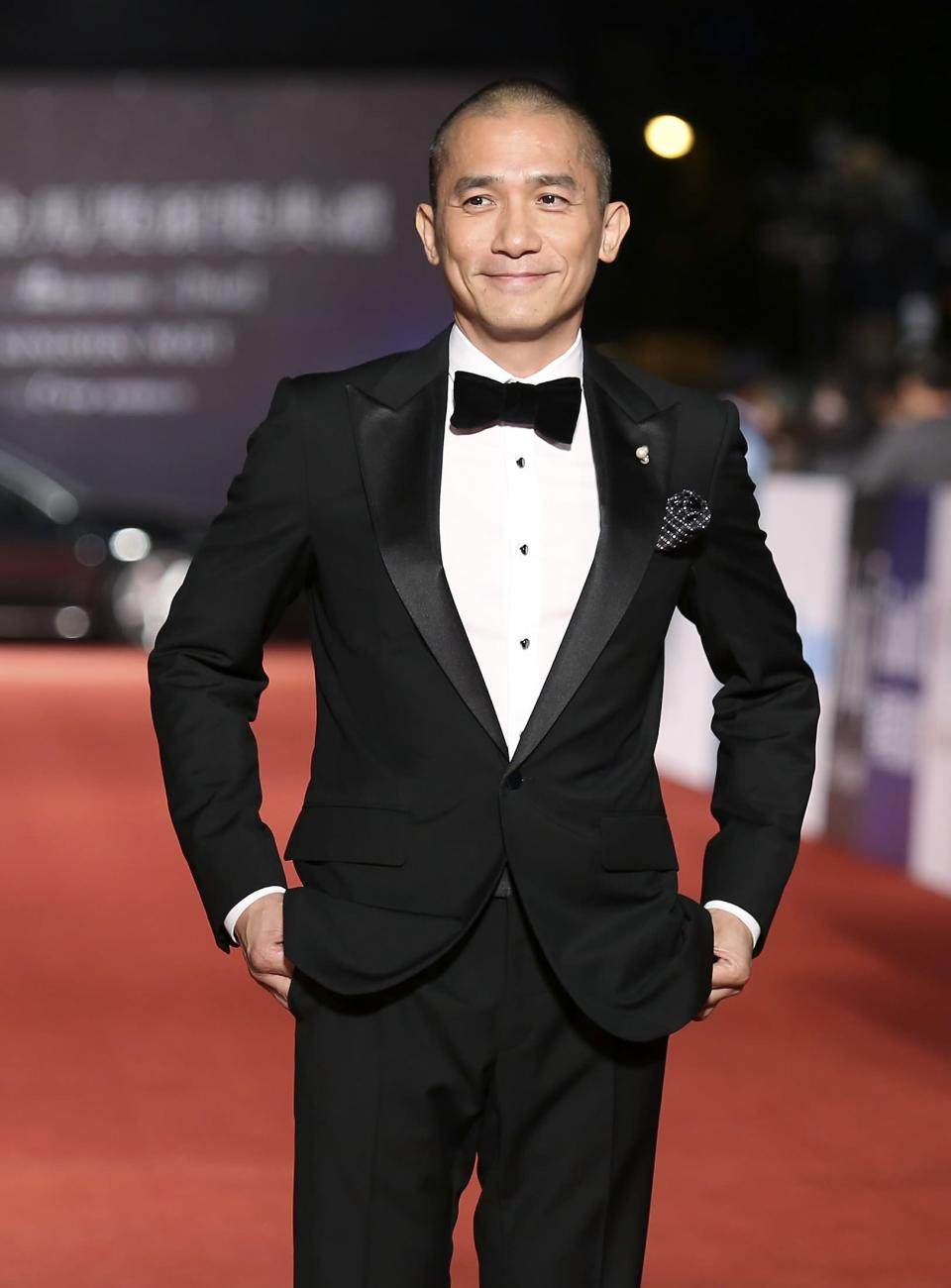 Hong Kong actor Tony Leung Chiu-wai poses for photographers on the red carpet at the 50th Golden Horse Film Awards in Taipei November 23, 2013. REUTERS/Patrick Lin (TAIWAN - Tags: ENTERTAINMENT)