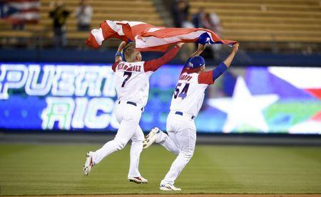 Mar 20, 2017; Los Angeles, CA, USA; Puerto Rico outfielder Enrique Hernandez (left) and Puerto Rico pitcher Hiram Burgos (54) celebrate after winning against Netherlands during the 2017 World Baseball Classic at Dodger Stadium. Puerto Rico won 4-3. Kelvin Kuo-USA TODAY Sports