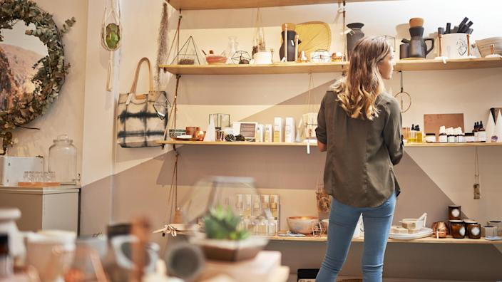 Rearview shot of a young woman looking at products on a shelf in a store.