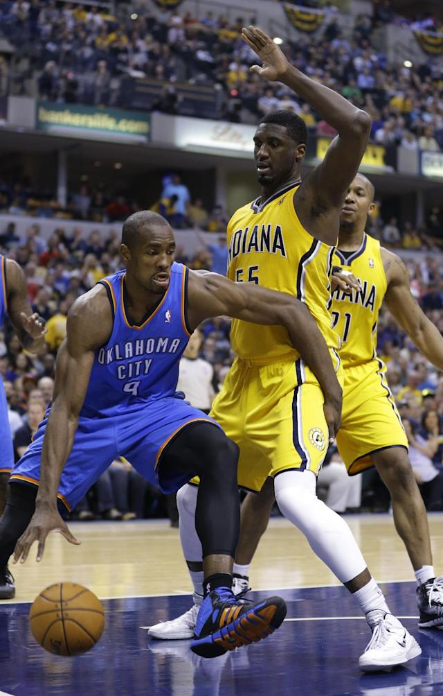 Oklahoma City Thunder forward Serge Ibaka, left, drives around Indiana Pacers center Roy Hibbert in the first half of an NBA basketball game in Indianapolis, Sunday, April 13, 2014. (AP Photo/Michael Conroy)