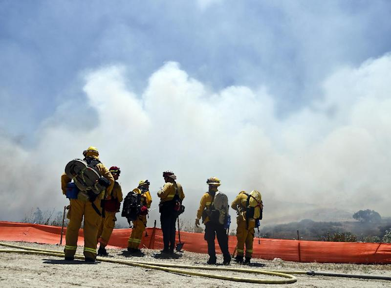 Firefighters face a huge smoke cloud as they plan their attack on a wild fire Tuesday, May 13, 2014, in San Diego. Wildfires destroyed a home and forced the evacuation of several others Tuesday in California as a high-pressure system brought unseasonable heat and gusty winds to a parched state that should be in the middle of its rainy season. (AP Photo)