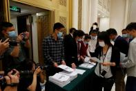 Journalists pick up a copy of China's National Bureau of Statistics population census report before a news conference in Beijing