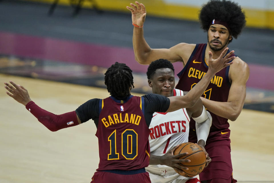 Houston Rockets' Victor Oladipo, center, drives to the basket between Cleveland Cavaliers' Jarrett Allen, right, and Cleveland Cavaliers' Darius Garland in the second half of an NBA basketball game, Wednesday, Feb. 24, 2021, in Cleveland. The Cavaliers won 112-96. (AP Photo/Tony Dejak)