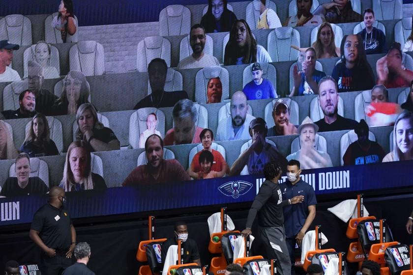 Photos of fans are seen on screens during the second half of an NBA basketball game between the New Orleans Pelicans and the Utah Jazz Thursday, July 30, 2020, in Lake Buena Vista, Fla. (AP Photo/Ashley Landis, Pool)