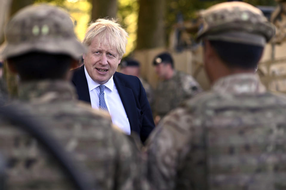 """Britain's Prime Minister Boris Johnson talks to Ghurkas as he meets with military personnel on Salisbury Plain training area near Salisbury, England, Thursday, Sept. 19, 2019. British Prime Minister Boris Johnson was accused by a one of the country's former leaders of a """"conspicuous"""" failure to explain why he suspended Parliament for five weeks, as a landmark Brexit case at the U.K. Supreme Court came to a head on Thursday. (Ben Stansall/Pool Photo via AP)"""