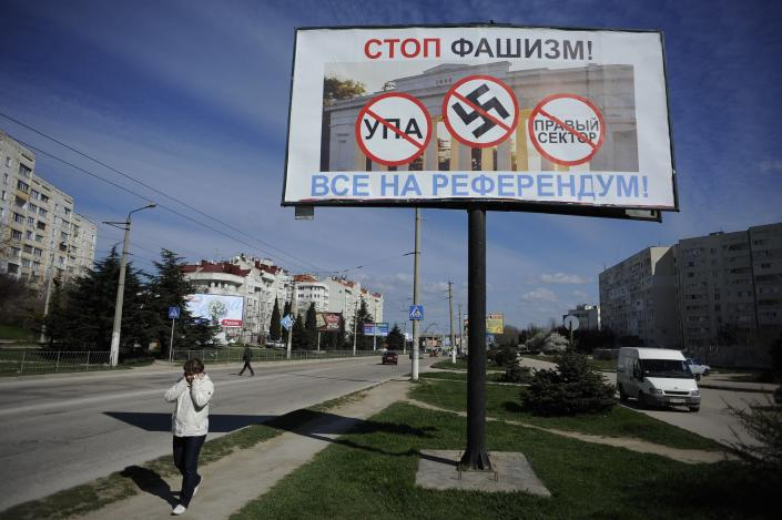 """A resident walks by a poster reading """"Stop fascism! Everybody to the referendum!"""" in Sevastopol, Ukraine Thursday, March 13, 2014. Crimea plans to hold a referendum on Sunday that will ask residents if they want the territory to become part of Russia. Ukraine's government and Western nations have denounced the referendum as illegitimate and warned Russia against trying to annex Crimea. (AP Photo/Andrew Lubimov)"""