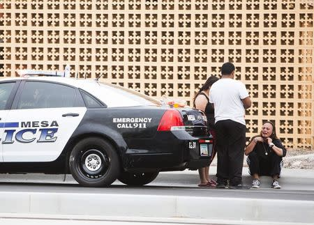 Tanya Ehrig, who claimed in a TV interview that her sister's boyfriend was a victim, sits near a police car at one of the scenes of a multiple location shooting that has injured at least four people in Mesa, Arizona March 18, 2015. REUTERS/Deanna Dent
