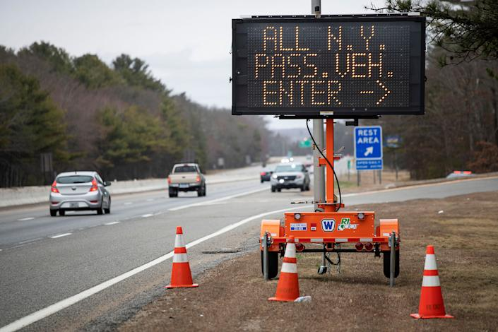 A sign tells motorists with New York license plates to pull over at a checkpoint on I-95 in Rhode Island. (Photo: ASSOCIATED PRESS)