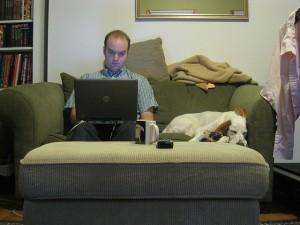 Man with dog and laptop on couch