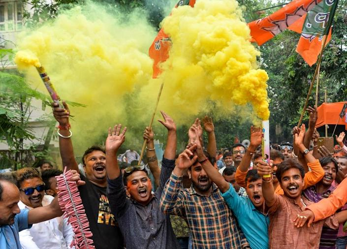 Supporters of the Bharatiya Janata Party (BJP) hold coloured smoke crackers in celebration as a preliminary vote count predicts a commanding lower house majority for Indian Prime Minister Narendra Modi's party and its allies after national elections (AFP Photo/DIPTENDU DUTTA)