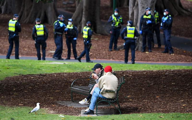 A couple enjoy a break while police patrol through Treasury Gardens in Melbourne - AFP