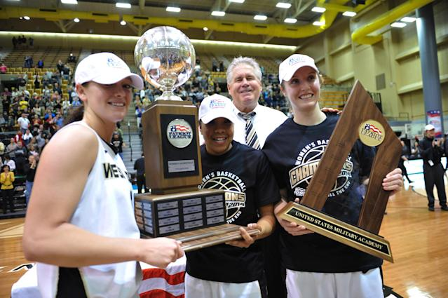 Army women's basketball team captains, from left in the foreground, Jen Hazlett, Jordan Elliott and Olivia Schretzman, and head coach Dave Magarity, background, stand for a portrait after winning the NCAA college basketball game in the Patriot League Championship game against Holy Cross at Christi Arena, Saturday, March 15, 2014, at West Point, N.Y. Army won 68-58. (AP Photo/Karl Rabe)