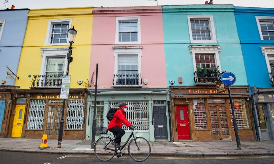 A cyclist wearing a face mask rides past closed up shops on Portobello Road in west London