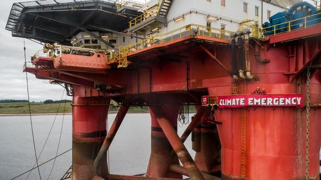 Banner and protesters on oil rig