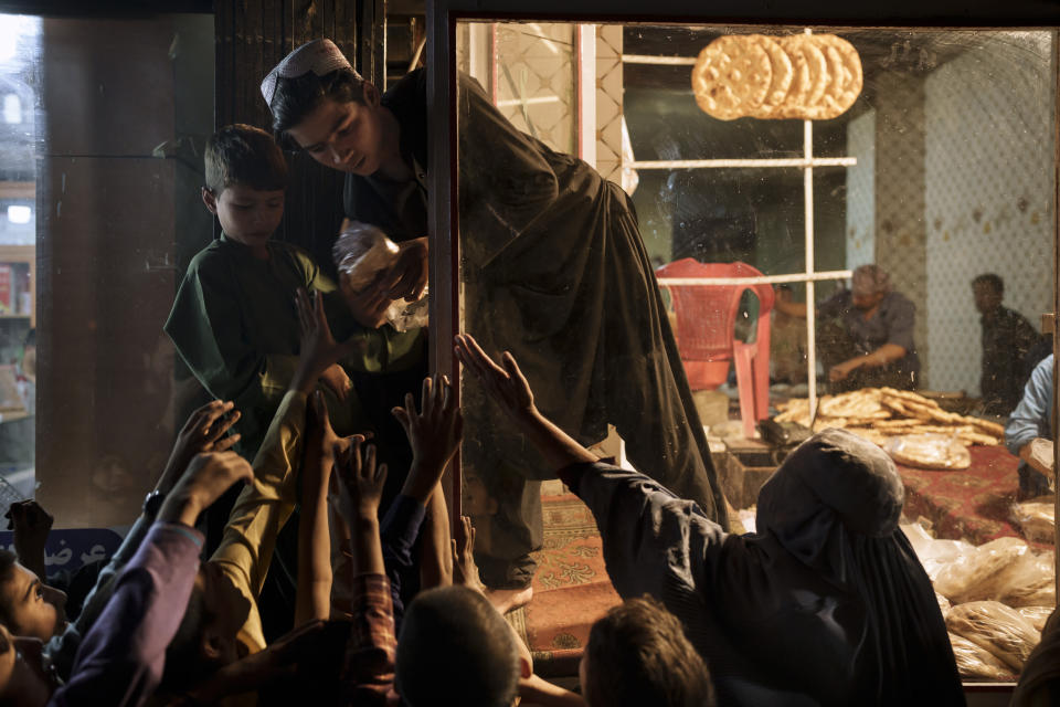 Afghan children and women gather outside a bakery to get free bread in Kabul, Afghanistan, Friday, Sept. 24, 2021. (AP Photo/Felipe Dana)