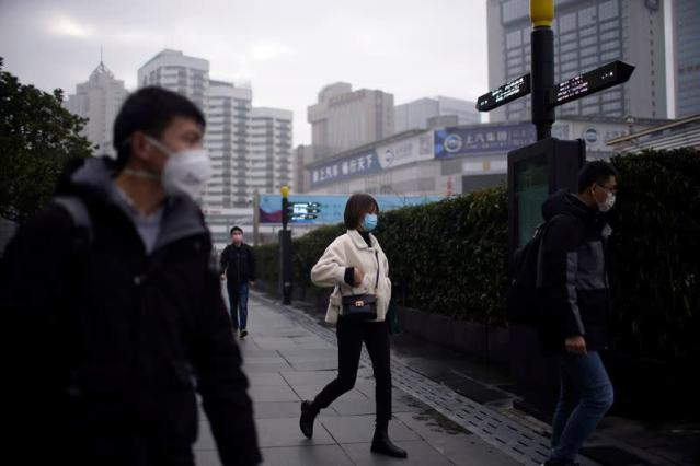 FILE PHOTO: People wearing masks are seen at a square in Shanghai