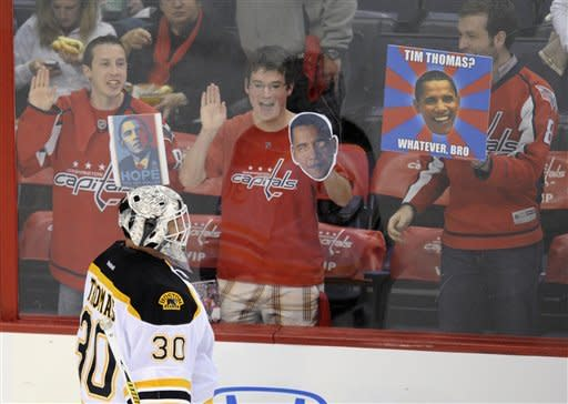 Boston Bruins goalie Tim Thomas (30) skates during warm-ups as fans hold signs before Game 3 of an NHL hockey Stanley Cup first-round playoff series between the Bruins and the Washington Capitals, Monday, April 16, 2012, in Washington. (AP Photo/Nick Wass)