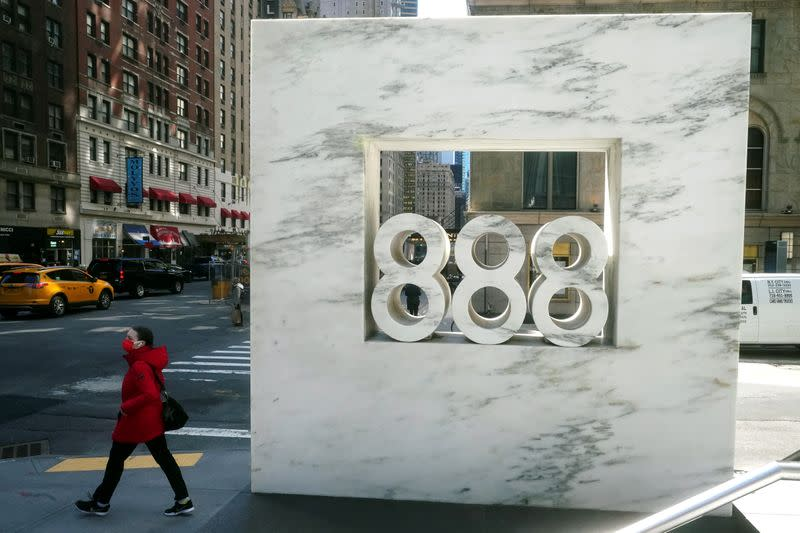 FILE PHOTO: A person walks past 888 7th Ave, a building that reportedly houses Archegos Capital in New York City