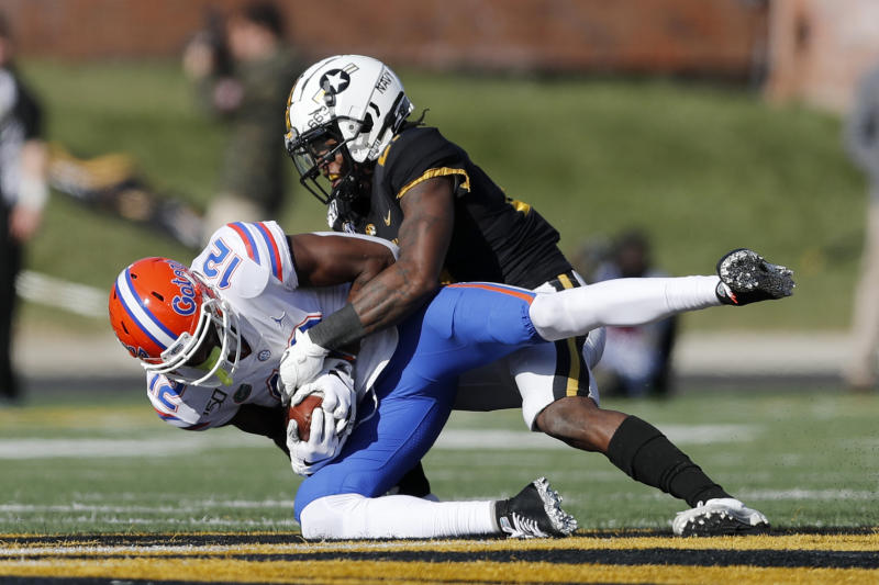 Florida wide receiver Van Jefferson (12) is pulled down by Missouri defensive back Christian Holmes after catching a pass during the second half of an NCAA college football game Saturday, Nov. 16, 2019, in Columbia, Mo. Florida won 23-6. (AP Photo/Jeff Roberson)