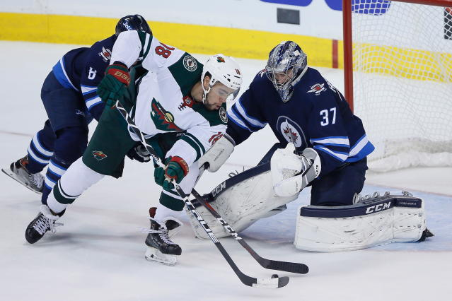 Minnesota Wild's Jordan Greenway (18) can't get the puck past Winnipeg Jets goaltender Connor Hellebuyck (37) during the first period in Game 5 of an NHL hockey first-round playoff series in Winnipeg, Manitoba, Friday, April 20, 2018. (John Woods/The Canadian Press via AP)