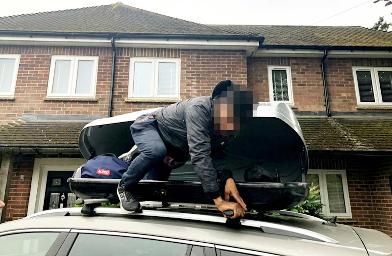 The young stowaway pictured clambering out of Simon Fenton's family car's roof box in Newbury, Berkshire. (SWNS)