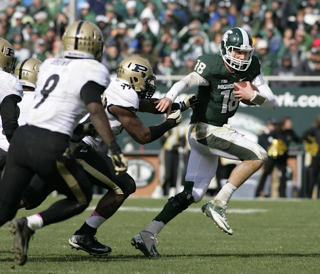 FILE - In this Oct. 19, 2013 file photo, Michigan State quarterback Connor Cook (18) scrambles against Purdue's Ryan Russell, center, and Anthony Brown (9) during the fourth quarter of an NCAA college football game in East Lansing, Mich. Heading into the final month of regular season Michigan State is battling for supremacy in the Big Ten's Legends Division with Michigan and Nebraska. (AP Photo/Al Goldis, File)