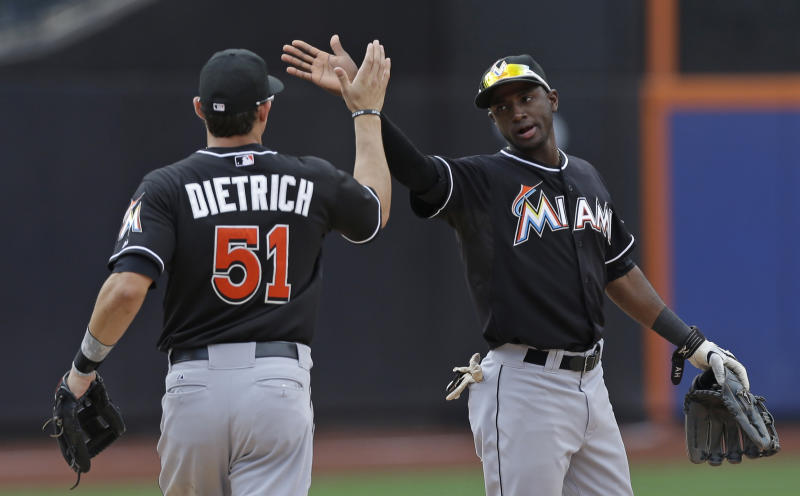 Miami Marlins shortstop Adeiny Hechavarria, right, celebrates the Marlins 8-4 victory over the New York Mets with Miami Marlins second baseman Derek Dietrich (51) at the conclusion of their baseball game in New York, Sunday, June 9, 2013. (AP Photo/Kathy Willens)