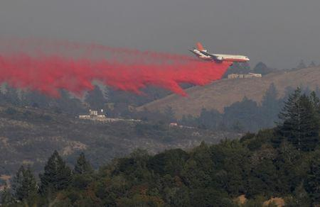 An air tanker drops retardant to contain a wildfire outside Santa Rosa, California, U.S., October 15, 2017. REUTERS/Jim Urquhart