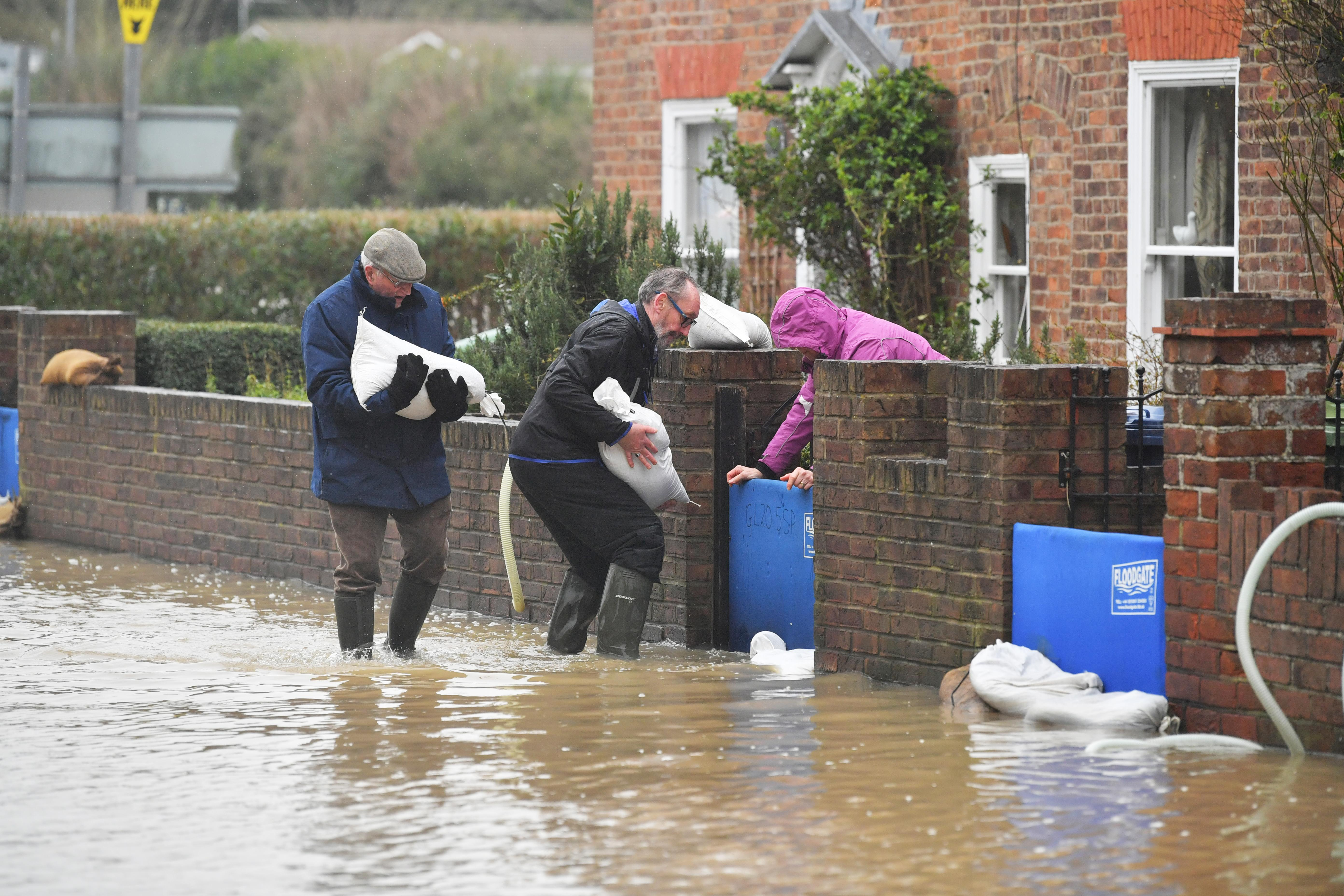 Residents picking up sandbags in Gloucester Road in Tewkesbury, Gloucestershire, where pumps and flood barriers have been put in to help to keep the water from flooding homes following the aftermath of Storm Dennis.