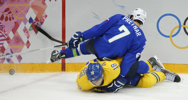 Slovenia defenseman Klemen Pretnar (7) falls on top of Sweden forward Jakob Silfverberg in the second period of a men's ice hockey game at the 2014 Winter Olympics, Wednesday, Feb. 19, 2014, in Sochi, Russia. (AP Photo/Mark Humphrey)