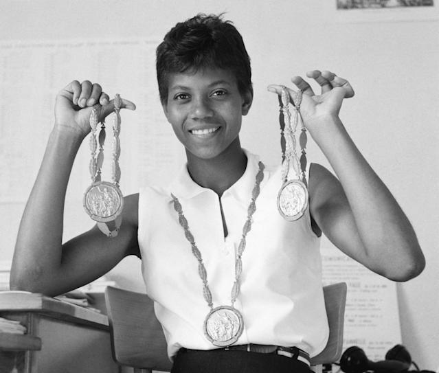 Sprinter Wilma Rudolph wears one gold medal and holds up the two others she won at the 1960 Summer Olympics in Rome. (Getty Images)