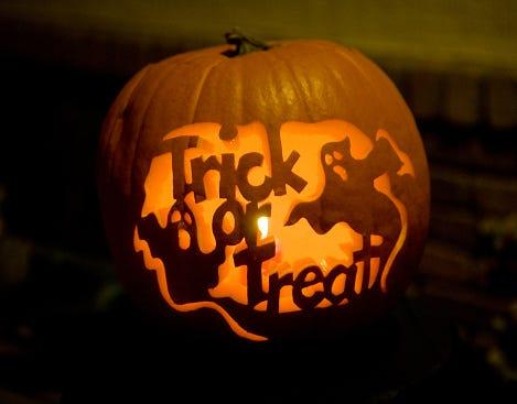 "A pumpkin carving in the shape of ghosts and the words ""Trick or Treat"""