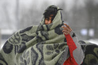 A migrant wraps himself in a blanket while walking through the snow at the Lipa camp northwestern Bosnia, near the border with Croatia, Saturday, Dec. 26, 2020. Hundreds of migrants are stranded in a burnt-out squalid camp in Bosnia as heavy snow fell in the country and temperatures dropped during a winter spell of bad weather after fire earlier this week destroyed much of the camp near the town of Bihac that already was harshly criticized by international officials and aid groups as inadequate for housing refugees and migrants.(AP Photo/Kemal Softic)