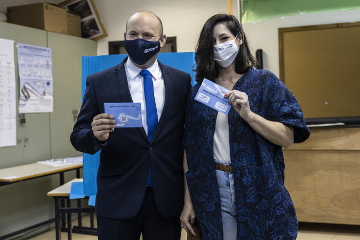 Israeli politician Naftali Bennett, leader of the right wing 'New Right' party, and his wife Gilat vote in the city of Raanana, Israel, Tuesday, March 23, 2021. (AP Photo/Tsafrir Abayov)
