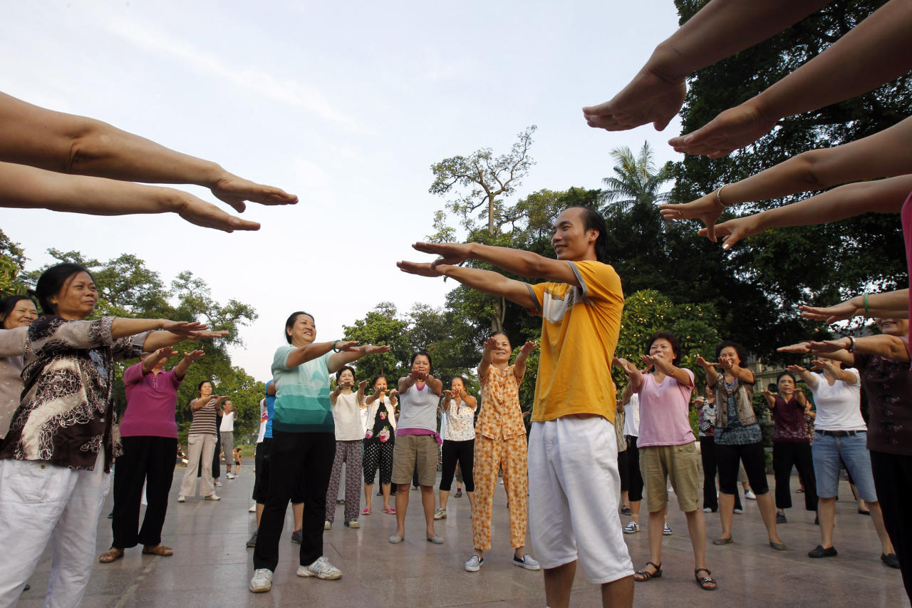 Yoga master Le Anh Son (C) and members of the Laughter Yoga club stretch out their arms during morning exercise at a public park in Hanoi September 24, 2011. For the past two years, several hundred people have been gathering each morning at a public park in central Hanoi to practise laughing under the instruction of Son in the belief that this will help them to be happier, fight disease and relief the stresses of daily life. Laughter yoga was launched in 1995 by Dr. Madan Kataria, a physician, in India and there are now more than 6,000 clubs in 60 countries, Son said. REUTERS/Kham