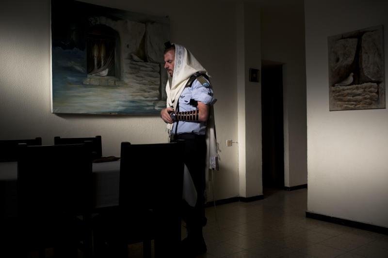 In this photo taken Wednesday, April 30, 2014, Jewish ultra-Orthodox military captain Moshe Prigan, performs his morning prayer at home in the ultra-Orthodox Jewish town of Bnei Brak, near Tel Aviv, Israel. Prigan doesn't just serve in the Israeli military, he also recruits other ultra-Orthodox Jewish men to enlist, something the cloistered community has traditionally avoided doing. The issue of military service is at the core of a cultural war over the place of ultra-Orthodox Jews in Israeli society today. (AP Photo/Oded Balilty)