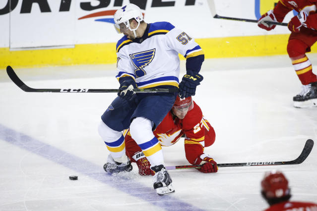 St. Louis Blues' David Perron, left, is checked by Calgary Flames' Sean Monahan during the third period of an NHL hockey game in Calgary, Saturday, Nov. 9, 2019. (Jeff McIntosh/The Canadian Press via AP)