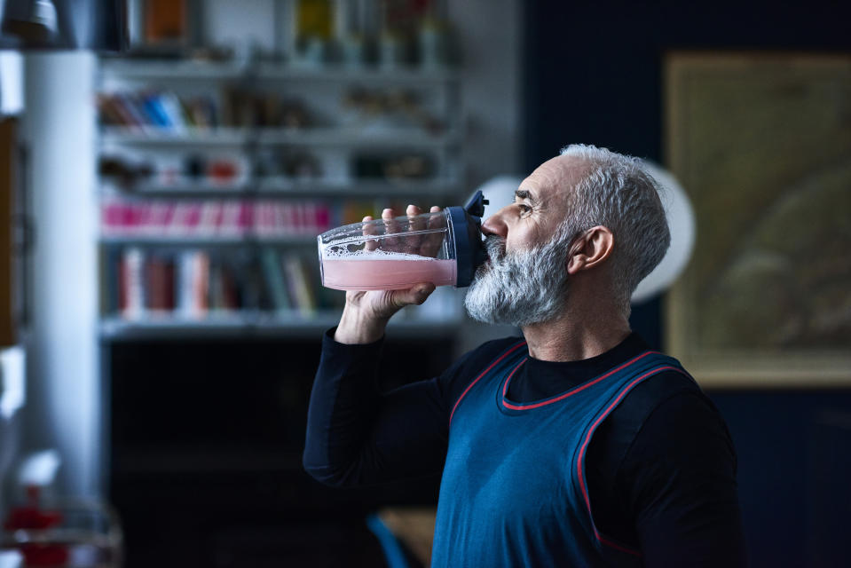 Side view portrait of active man in his 50s drinking pink liquid fruit juice, head and shoulders, grey hair and beard, back from morning run, recovering, thirsty