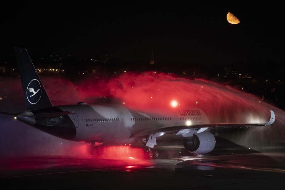 The last Lufthansa flight of the Airbus A350 aircraft from Tegel Airport is taxiing to the take-off field as it is bid farewell by the airport fire brigade with a fountain of water in Berlin, Germany, Saturday, Nov. 7, 2020. The final flight is scheduled for Sunday. (Fabian Sommer/dpa via AP)