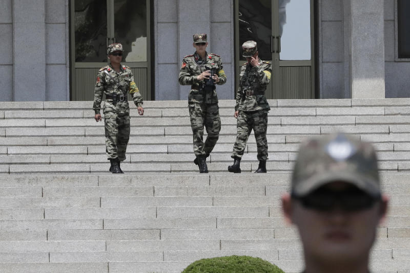 In this June 12, 2019, photo, North Korean soldiers look at the South side as a South Korean soldier, foreground right, stands during a press tour at the border village of Panmunjom in the Demilitarized Zone, South Korea. South Korea says two of four North Korean fishermen who were rescued off a boat drifting in South Korean waters will remain in the country after expressing their desire to defect. Seoul's Unification Ministry on Tuesday, June 18, 2019 said the two other fishermen were sent back to North Korea through the inter-Korean village. (AP Photo/Lee Jin-man)
