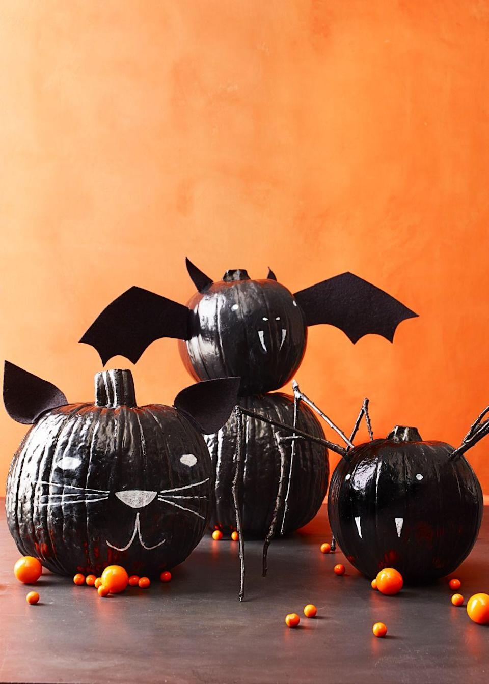 """<p>Create a group of creepy crawlers with a two coats of chalkboard paint. Once they dry, use white chalk to draw on a cat's face. Finish by hot-gluing on <a href=""""https://www.amazon.com/Darice-FLT-0332-Stiff-Sheet-Black/dp/B0054G5JT2?tag=syn-yahoo-20&ascsubtag=%5Bartid%7C10055.g.1714%5Bsrc%7Cyahoo-us"""" rel=""""nofollow noopener"""" target=""""_blank"""" data-ylk=""""slk:black felt"""" class=""""link rapid-noclick-resp"""">black felt</a> ears. For the bat, glue on felt wings. And for the spider, paint eight twigs and make holes around the top of the pumpkin with a screwdriver. Position the sticks in the holes and secure with hot glue.</p><p><a class=""""link rapid-noclick-resp"""" href=""""https://www.amazon.com/Rust-Oleum-1913830-6-PK-Chalkboard-1913830/dp/B01MTDQTLJ/ref=sr_1_2?tag=syn-yahoo-20&ascsubtag=%5Bartid%7C10055.g.1714%5Bsrc%7Cyahoo-us"""" rel=""""nofollow noopener"""" target=""""_blank"""" data-ylk=""""slk:SHOP CHALKBOARD PAINT"""">SHOP CHALKBOARD PAINT</a><br></p>"""