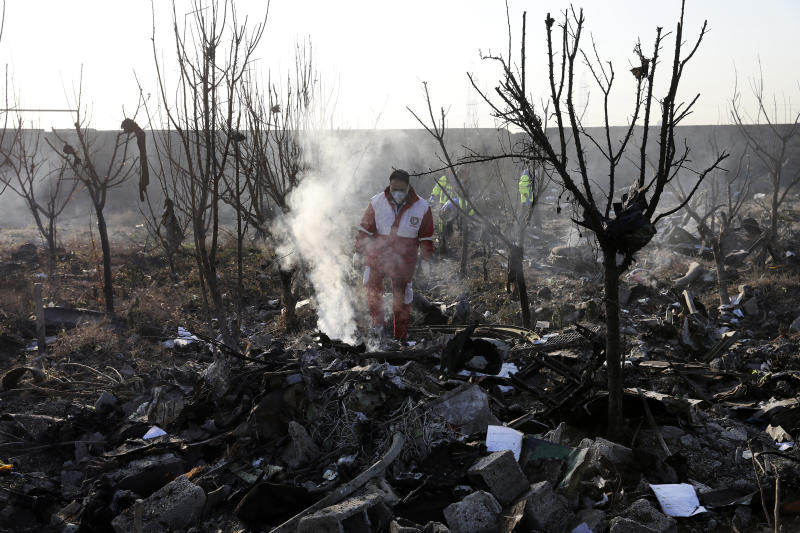 Rescue workers search the scene where an Ukrainian plane crashed in Shahedshahr, southwest of the capital Tehran, Iran, Wednesday, Jan. 8, 2020. A Ukrainian airplane carrying 176 people crashed on Wednesday shortly after takeoff from Tehran's main airport, killing all onboard. (AP Photo/Ebrahim Noroozi)