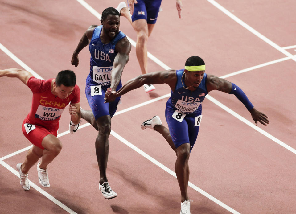 Justin Gatlin of the United States, center, passes the baton to Michael Rodgers in the men's 4x100 meter relay final at the World Athletics Championships in Doha, Qatar, Saturday, Oct. 5, 2019. (AP Photo/Nariman El-Mofty)