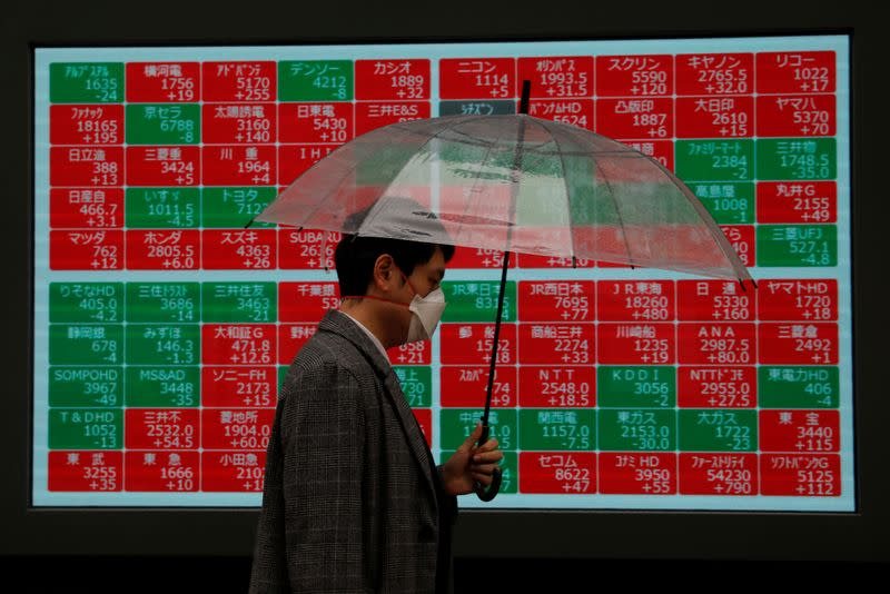 A visitor wearing protective face mask, following an outbreak of the coronavirus, walks past in front of a stock quotation board outside a brokerage in Tokyo