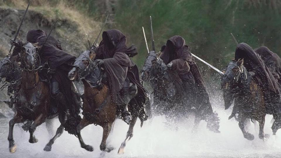 The hooded Nazgul ride their horses through a river in a scene from The Lord of the Rings: The Fellowship of the Ring.