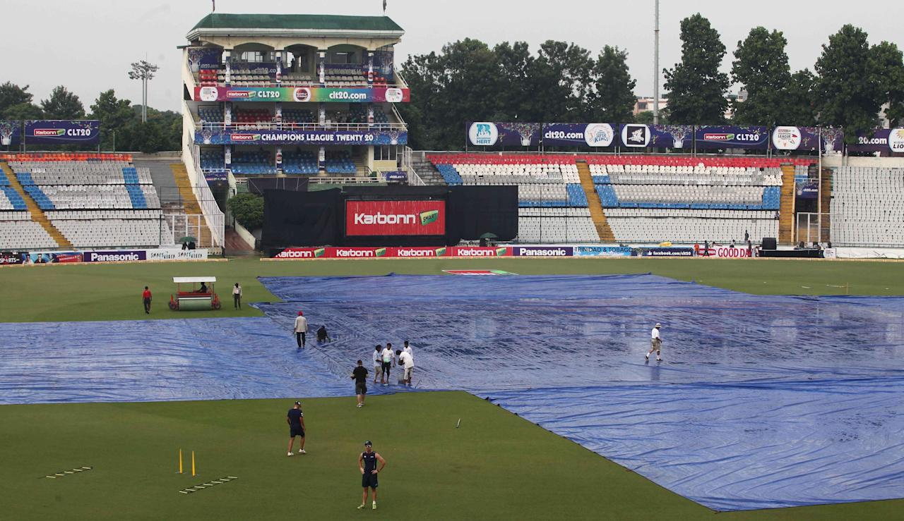 The ground staff at work hard in Mohali stadium ahead of Champions League T20, 6th match, Group B, between Brisbane Heat and Titans which was delayed by 45 minutes due to rain on Sept. 24, 2013. (Photo: IANS)