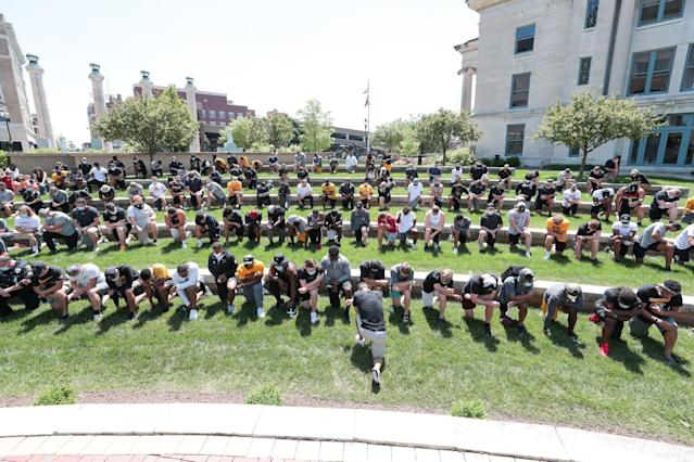 Missouri football players take a knee after marching along with basketball coach Cuonzo Martin, president Mun Choi and other members of the athletic department. (Photo credit: Missouri Athletics)