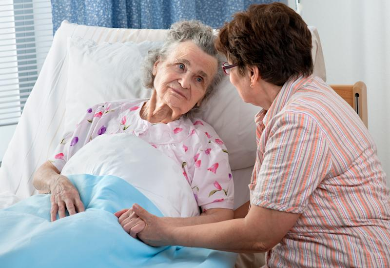 Older woman in bed while another woman sits with her, holding her hand